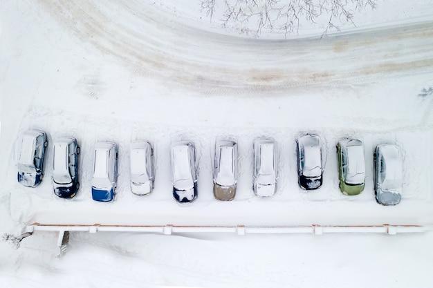Ośnieżone samochody na parkingu widok z tronu z góry.