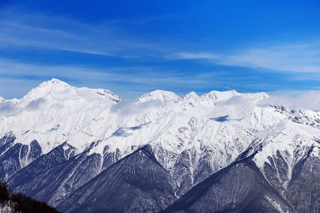Ośnieżone szczyty gór kaukazu. piękne widoki na ośrodek narciarski rosa khutorin. zima krajobraz z niebieskim niebem.