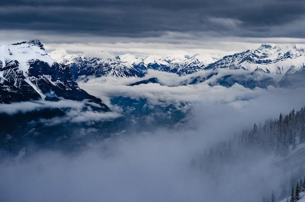 Ośnieżone szczyty skalistych gór pod zachmurzonym niebem