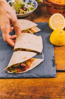 Osob ręka bierze plasterek meksykański wołowina tacos
