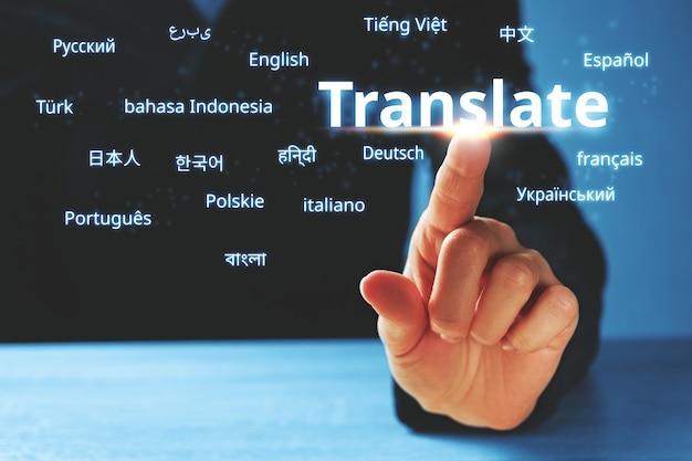 Osoba abstrakcyjnie naciska na wyświetlacz ze słowem tłumacz i językami obcymi.