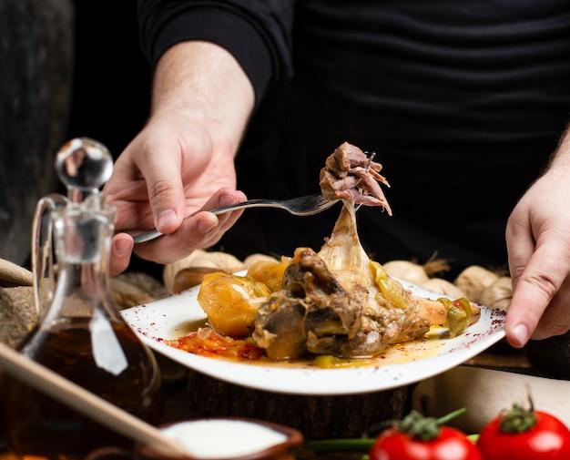 Osoba biorąca mięso z talerza z ziemniakami, ziołami i przyprawami