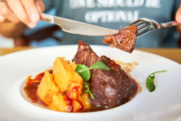 Osoba chwytająca kawałek mięsa wykrojony z naczynia z policzków cielęcych z kokosowym mojo i puree z tuńczyka z sosem pomarańczowym podanym w białym ceramicznym talerzu na drewnianym stole