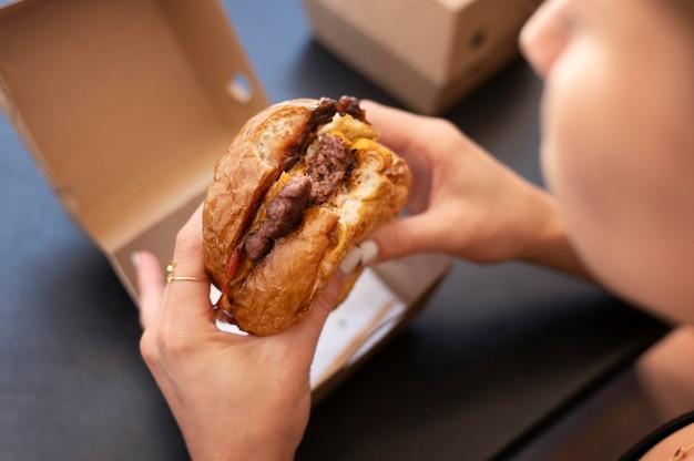 Osoba ciesząca się burgerem na wynos