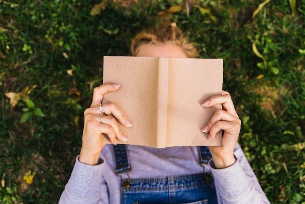Osoba czytająca na trawie