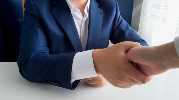 Osoba dająca łapówkę urzędnikowi, jednocześnie podając mu rękę