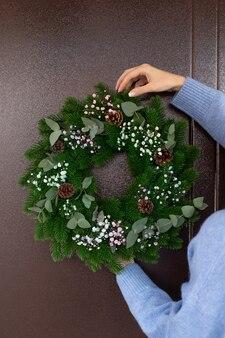 Osoba dekorująca drzwi wejściowe wieńcem świątecznym świąteczna dekoracja świąteczna nowego roku