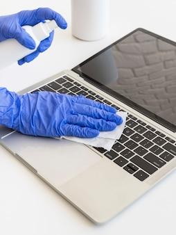 Osoba dezynfekująca laptopa