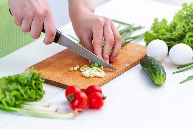 Osoba do gotowania w fartuchu sieka ekologiczne produkty na sałatkę ze świeżych zdrowych warzyw w kuchni w domu.