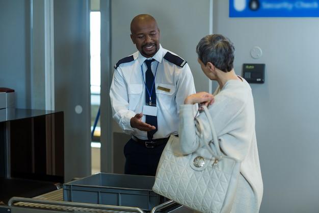 Osoba dojeżdżająca do pracy, która sprawdza bagaż od oficera ochrony lotniska