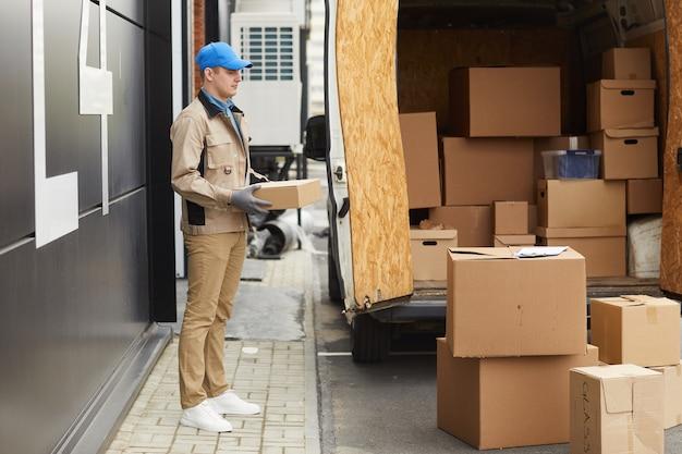 Osoba dostarczająca ładująca pudełka do furgonetki pracuje w magazynie dostaw