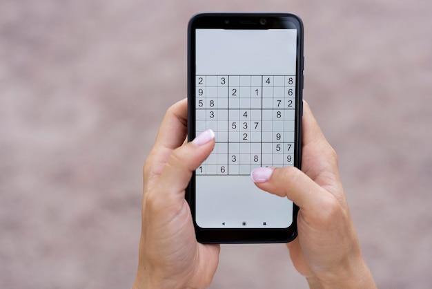 Osoba grająca w sudoku na smartfonie