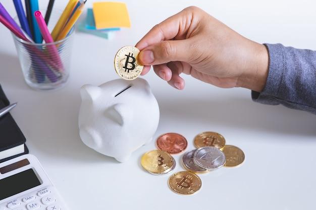Osoba handlująca lub oszczędnościowa kryptowalutą z bitcoinem i skarbonką.finanse i technologia