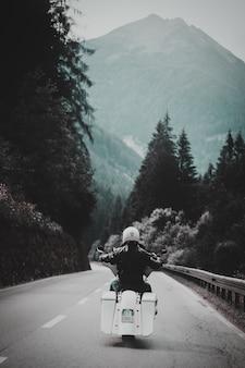 Osoba jadąca białym motocyklem wzdłuż utwardzonej drogi