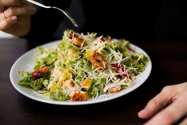 Osoba je smakowitą caesar sałatki z croutons w restauraci