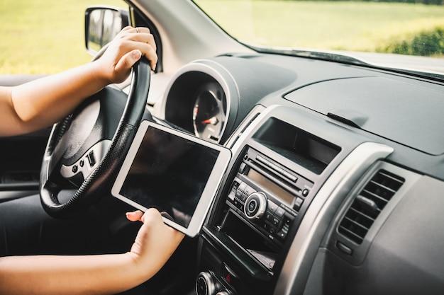 Osoba kierująca i trzymając tabletkę
