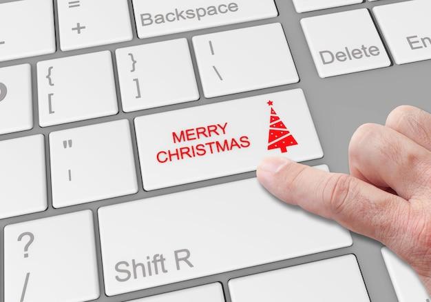"""Osoba klikająca specjalny przycisk """"wesołych świąt"""" na klawiaturze laptopa"""