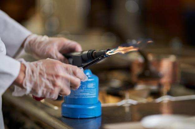 Osoba korzystająca z palnika gazowego w kuchni