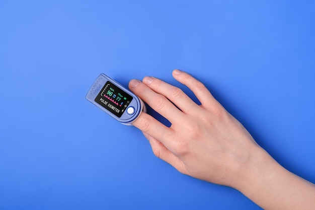 Osoba korzystająca z pulsoksymetru na palcu, koncepcja monitorowania opieki zdrowotnej