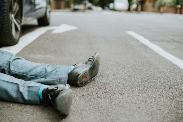Osoba leżąca na ziemi po wypadku samochodowym
