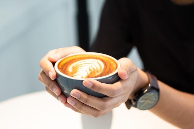 Osoba ma filiżankę kawy
