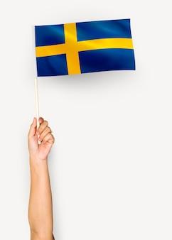Osoba machająca flagą królestwa szwecji