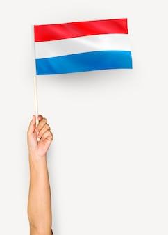 Osoba machająca flagą wielkiego księstwa luksemburga