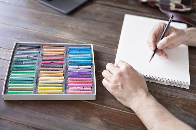 Osoba malująca kredą pastelową na białej kartce papieru z paletką kredek pastelowych na drewnianym stole