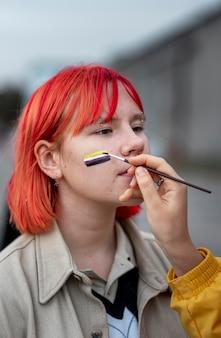 Osoba malująca niebinarną flagę na przyjacielu na zewnątrz