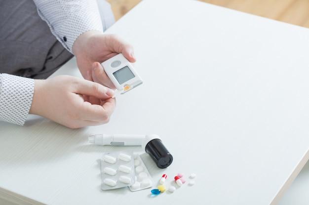 Osoba mierzy poziom cukru we krwi za pomocą glukometru
