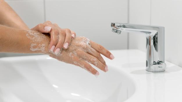 Osoba myjąca ręce z boku