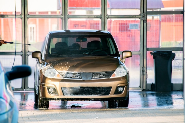 Osoba myjąca samochód na stacji ze specjalnym środkiem czyszczącym, usługi myjni samochodowej