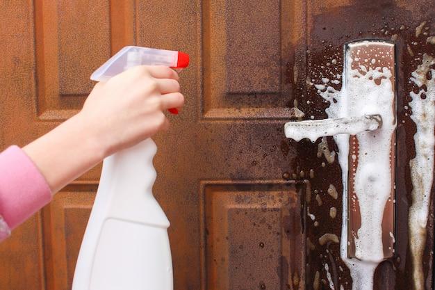 Osoba myje klamkę drzwi wejściowych.