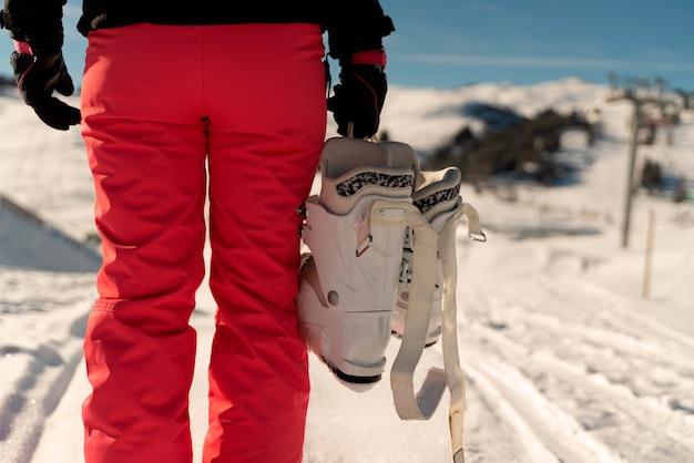 Osoba na plecach w różowych spodniach narciarskich trzymająca buty narciarskie w ośrodku narciarskim w alpach