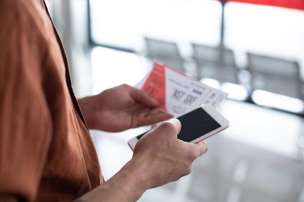 Osoba na stacji patrząca na bilet i sprawdzająca go telefonem komórkowym