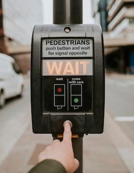 Osoba naciskająca przycisk krzyża dla pieszych