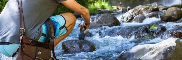 Osoba nad rzeką robiąca zdjęcie telefonem wodospadu. turrialba, kostaryka