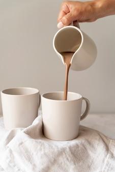 Osoba nalewa kawę w białej filiżance