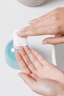 Osoba nalewa mydło w dłoń