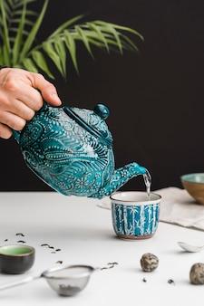 Osoba nalewająca herbatę w szklance wody