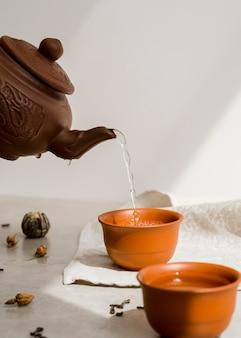 Osoba nalewająca herbatę z glinianego czajnika