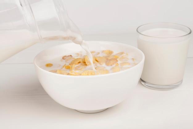 Osoba nalewająca mleko w misce z mlekiem