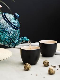 Osoba nalewanie herbaty z czajniczek w filiżance