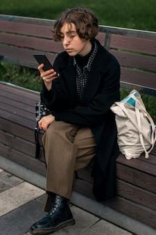 Osoba niebinarna sprawdzająca telefon siedząc na ławce