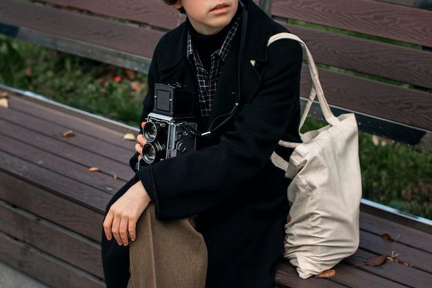 Osoba niebinarna trzymająca retro aparat siedząc na ławce