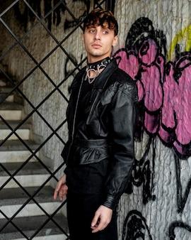 Osoba niebinarna w skórzanej kurtce pozująca obok ściany z graffiti