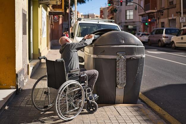Osoba niepełnosprawna na wózku inwalidzkim podnosi przezroczystą plastikową butelkę wyrzuconą i porzuconą na podłogę, aby wrzucić ją do pojemnika na śmieci i uniknąć zanieczyszczenia. unikaj tworzyw sztucznych