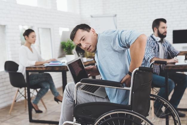 Osoba niepełnosprawna na wózku inwalidzkim pracuje w biurze.