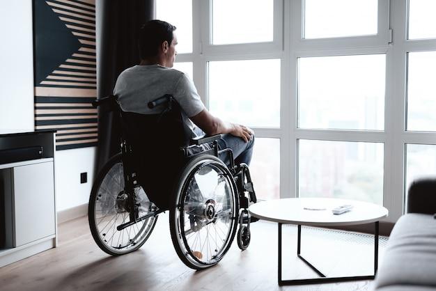 Osoba niepełnosprawna na wózku inwalidzkim siedzi z przodu.