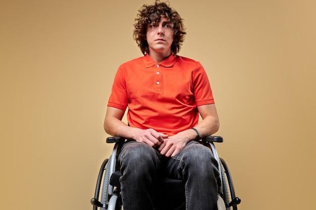 Osoba niepełnosprawna na wózku inwalidzkim wygląda na zdenerwowaną, nie ma sensu życia, cierpi na niepełnosprawność. portret. na białym tle beżowym tle